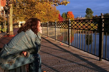 A woman sits along the riverfront in downtown Allegan in this file photograph. Allegan officials have plans to improve riverfront parks by using $500,000 from a city sinking fund as start-up money.