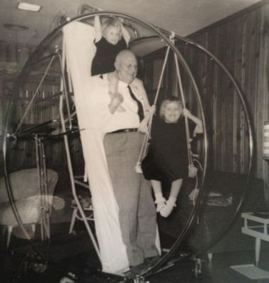 A 1958 photo of Dr. Homer Stryker, founder of Stryker Corp., with his granddaughters, Patricia, 2, on his shoulders, and Ronda, 4. They are pictured with a Circo Lectic Bed, one of Stryker's most famous inventions.
