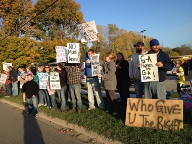 Protesters wave signs in front of the Galesburg-Augusta Community Schools bus garage on Oct. 10. They were upset by an incident in which the transportation supervisor threw a 7-year-old against an inside wall of the bus.