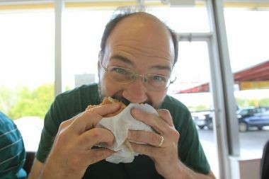 David Kutzko, of Kalamazoo, is John Gonzalez's companion on the Michigan's Best burger tour. Here is bites into his burger at Clyde's Drive-In in St. Ignace.