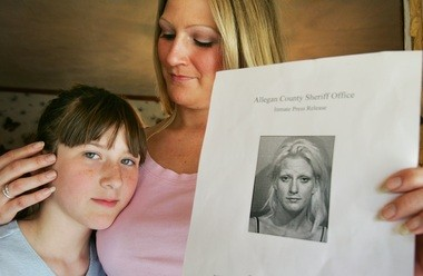 Amy Reed, with her 10-year-old daughter Taylor Hildebrand at their Allegan County home, in April 2005. A recovering meth addict in Allegan County's diversion program at the time, she is shown holding a booking mugshot.