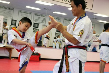 In this file photo from 2010, Walker Broadbent, 8, performs a high kick with instructor Grand Master Sun Hwan Chung at Chung's Black Belt Academy Tuesday. Broadbent, a red belt, will compete in his second Michigan Cup Saturday at Hackett Catholic Central High School.