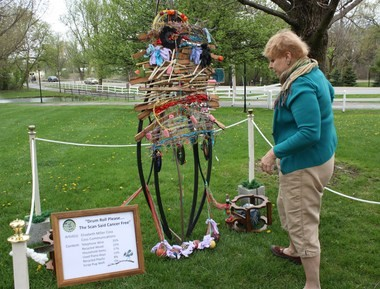 """Elizabeth Miller Coss assembles her entry on Friday in this year's second annual Portage Recycled Art Contest at Celery Flats. Coss, who won last year's top prize, calls this year's entry """"Drum Roll Please...The Scan Said Cancer Free."""""""