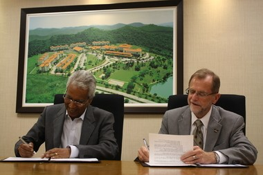 Western Michigan University President John Dunn, right, signs an Articulation Transfer Agreement with Nilai University College Professor Dato' Dr. Sothi Rachagan during a ceremony at the college in Malaysia.