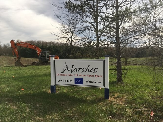 A sign for AVB's Marshes community is posted nearby an excavator where a dozen homes will be built.