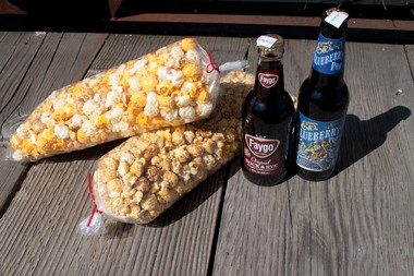 Pictured here is a mixed bag of cheddar cheese, white cheddar and caramel popcorn from Cravings Gourmet Popcorn, resting on a bag of cinnamon and caramel popcorn, along with two bottles of soda pop from the Old Town shop's collection.