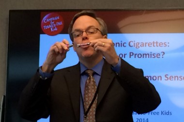Matthew Davis, chief medical executive for the Michigan Department of Community Health, holds up an electronic cigarette during a media briefing on March 4. 2014.