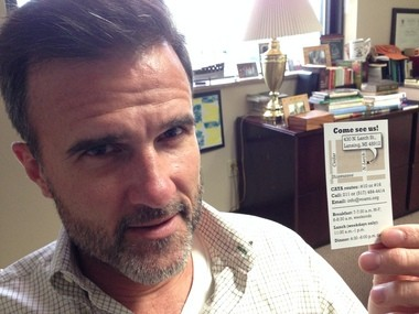 Patrick Patterson, executive vice president of the Volunteers of America, holds a card that the organization will start handing out to people in need.