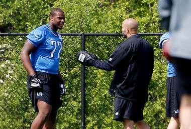 Detroit Lions offensive tackle Cornelius Lucas talks with assistant offensive line coach Bobby Johnson, the man who recruited Lucas to sign with Detroit as an undrafted free agent.