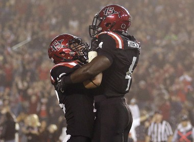 San Diego State running back Adam Muema, right, is lifted by teammate Bryce Quigley after scoring a touchdown against Fresno State.