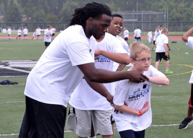 At his youth camp on Tuesday, Detroit Lions running back Joique Bell shows a participant the proper form to take a handoff.