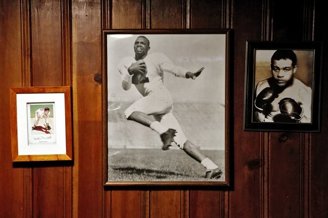 A photo collage of Wally Triplett, middle, boxer Joe Louis, right, and Philadelphia Stars infielder Mahlom Duckett, left, hangs in the basement of Triplett's home in Detroit (Mike Mulholland | MLive.com)