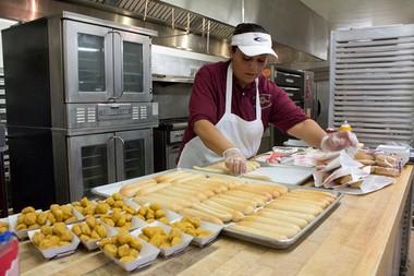 John Glenn High School Cook Rita 'Mona' Hewtty prepares mozzarella sticks and popcorn chicken for lunch on Tuesday, October 16, 2012.