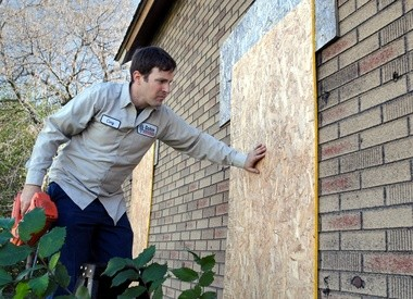 In this file photo, Cory L. Gohm, of Gohm Insurance Restoration, makes sure a boarded-up window is secure at an abandoned house at 2506 Thayer, in Saginaw.