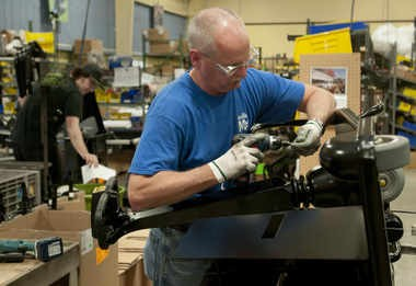 In this file photo, Dick Belill installs a drive and steering wheel on an Amigo scooter at the Amigo Mobility International Inc. plant in Bridgeport Township.