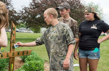 """James Bailey places a """"Drink and drive, you won't survive"""" card on a cross that students put up by the school sign to honor Ryon Lalonde Monday, June 2, at Bay City Western High School in Auburn. (Yfat Yossifor 