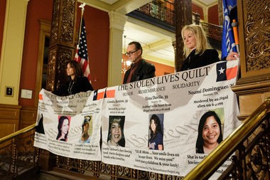 """From left, Maria Espinoza, national director of The Remembrance Project, an advocacy group that draws attention to Americans killed by undocumented immigrants, holds a """"Stolen Lives Quilt"""" along with Bay City resident Charles Congdon and Tamyra Murray, a local leader of Michiganders for Immigration Control and Enforcement."""