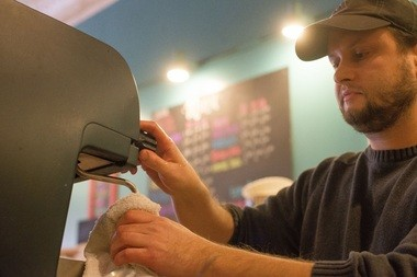Aaron Bolt, previous owner of Brewtopia, cleans an espresso machine Tuesday, Nov. 18, at the 810 Saginaw St. coffee shop in downtown Bay City. Kevin and Michele Clements recently purchased Brewtopia from Bolt.
