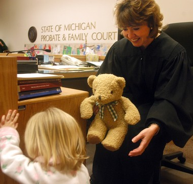 Judge Karen Tighe gives a new teddy bear to Hanna, 2, after her adoption confirmation ceremony on Michigan Adoption Day, November 25, 2003.