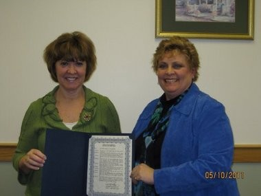 Bay County Probate Judge Karen Tighe (left) and District Judge Dawn A. Klida, holding an award granted by the Bay County Board of Commissioners, recognizing the success of the Drug Treatment Court in May 2011.
