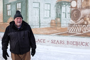 Bay City resident Bob Shea, who has worked for Sears on and off for the past 51 years, poses in front of the department store's former location on Saginaw Street in downtown Bay City. A mural depicting the birthplace of Sears is painted on the east side of the building, which is now home to F.P. Horak. Sears is closing its Bay City Mall location, putting an end to its more than 85-year-old history in Bay County. (Andrew Dodson | The Bay City Times)