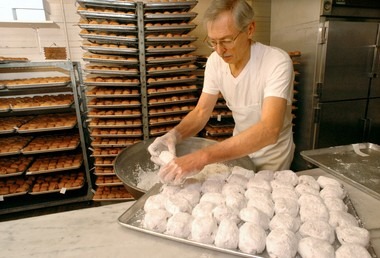 Michael Rezler coats a tray of paczki with powdered sugar at Sutherland's Bakery in this 2006 photo.