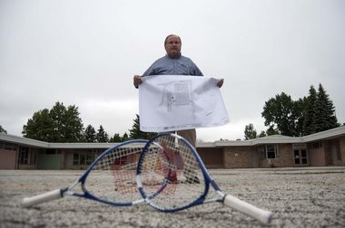 Gerald Schloff stands holding the blueprints for the proposed tennis courts at Thomas Jefferson School.