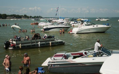 People wade by their boats Saturday, Aug. 15, at Boaters Beach in the Saginaw Bay.