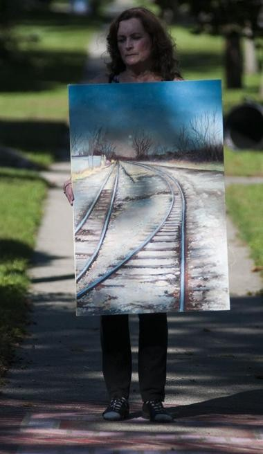 Rosemary Kavanagh holds her piece outside her home in Bay City, Saturday, Sept. 12, 2015. It's one of a two-painting entry for the seventh annual ArtPrize in Grand Rapids. This painting shows tracks on Water Street during a November evening. (Nicole Hester | The Bay City Times)