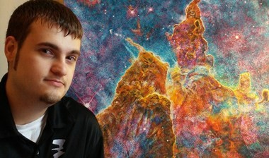 """Forrest Miller poses with one piece of a three-part series of oil paintings called """"Nebulae of Deep Space: Paintings celebrating the 25th anniversary of the Hubble Space Telescope,"""" the entry he submitted for the seventh annual ArtPrize."""
