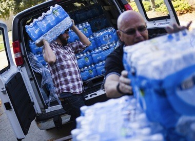 """Senior Minister Nathan Dannison, left, and Deacon Tom Birkhold of the 1st Congregational United Church of Christ in Kalamazoo help deliver more than 4,000 bottles of water for kids in the Flint School District on Wednesday, Sept. 30, 2015, at the Flint School District Administration Building in Flint. """"Flint is going to need a lot of water brought in,"""" said Birkhold, adding """"If the government can't do it, someone has to."""""""
