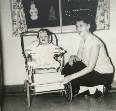 Steven Matich is shown in a carriage wearing a helmet after he was diagnosed with polio in 1954 at age 16 months. Next to him is his mother Betty Kochom.