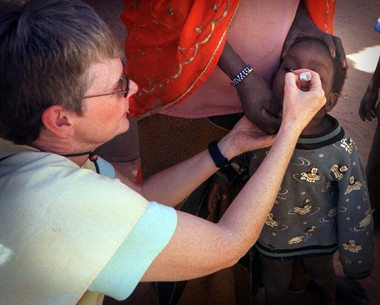 Nancy Cusick administers a polio vaccine to a child in Niger during a 2003 mission trip.
