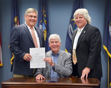 From left, state Sen. Mike Green, R-Mayville, Gov. Rick Snyder and Bay City Commissioner Lynn Stamiris, 1st Ward, pose for a photo after Snyder signed Green's bridge bill that sees the state reimburse Bay City for the operational costs of its two bascule bridges. While the city is going to realize $500,000 to $600,000 per year because of the bill to put toward local street repairs, it's also dealing with about $6 million in critical bridge repairs that need to take place within the next five years.