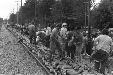 Volunteers build a sandbag barrier along the railroad tracks parallel to Westervelt Road south of Zilwaukee in September 1986.