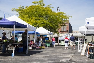 Vendors set up booths to sale their products during Bay City's farmers market at the intersection of Washington Ave. and Sixth Street Thursday June 9, 2016, in downtown Bay City.