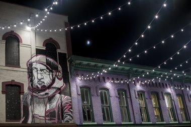 A mural painted by Detroit-based artist Paolo Pedini decorates the exterior of Jake's Corner Bar as the Third Street Star Bridge illuminates a section of Third Street between Saginaw Street and North Water Street in Bay City on July 12, 2016.