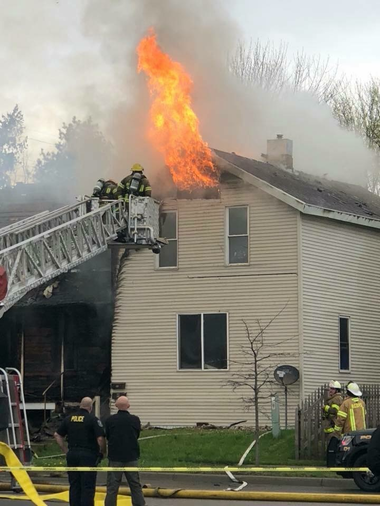 Firefighters battle a house fire Sunday, May 6, 2018, in the area of Salzburg Avenue and Warner Street in Bay City.