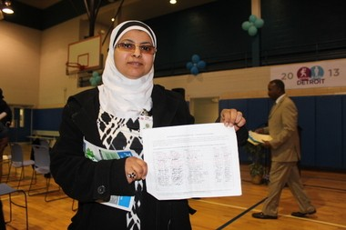 Aswan Almaktary, of southwest Detroit, displays petition signatures from residents hoping to keep open Romanowski Park.