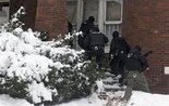 """The Detroit Police Department and other law enforcement agencies conduct a raid as part of """"Operation Mistletoe"""" on Detroit's west side Tuesday, Dec. 17, 2013. The raids targeted drugs houses, drug dealers and felons wanted for parole and probation violations, weapons charges, robberies, home invasions and assaults. (AP Photo/Detroit Free Press, Mandi Wright)"""