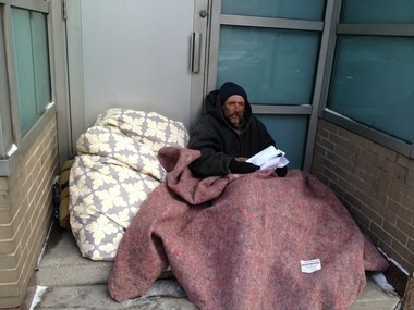 """John """"Boots"""" Black, a 53-year-old homeless man who describes himself as a chronic alcoholic, tries to keep warm under a blanket in subzero wind chill temperatures near Detroit City Hall on Monday, Jan. 6, 2014."""