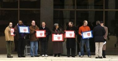 """A group in favor of gay marriage gathers in Grand Rapids' Calder Plaza in 2009, holding signs reading """"Liberty and Justice for all."""" The unofficial event was comprised of a few members from the Concerned Clergy of West Michigan and other citizens."""