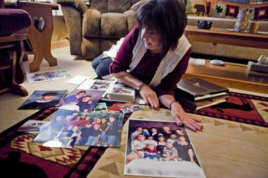 Patricia McLemore, mother of Patrick McLemore, who was convicted of first-degree murder at 16 and sentenced to life in prison in 2000, looks through photos in her Burton home. McLemore still holds out hope that her son will someday be freed.