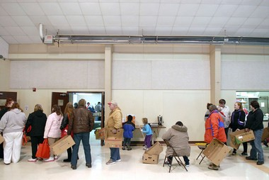 Those in need of assistance line up for a free food box at the Alanson Church of the Nazarene. The problem has grown more acute in recent years, its pastor says. (Bridge photo by John Russell)