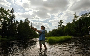 Roe Konopa casts her fly rod into the Au Sable River at the Gates AuSable Lodge east of Grayling during a session of Reeling and Healing of Michigan for women cancer survivors in 2003.