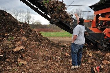 Don Butynski, a manager at the Ann Arbor compost center, pulls a branch from a Doppstadt slow-speed grinder used in the compost-making process.