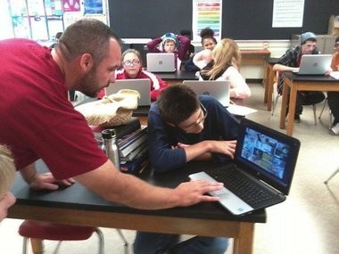 In this file photo, Orchard View Middle School teacher Ryan Wilson helps a student out with his computer during a robotics class the district added in 2014. (