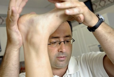 In this July 15, 2008, file photo, Larry Nassar, D.O., or Doctor of Osteopathy, works with a patient in East Lansing, MI. (Becky Shink/Lansing State Journal via AP, File)