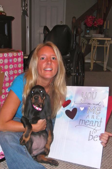 """Gabrielle Ford reacts to receiving her new coonhound companion to be named """"ILO"""" -- an acronym for """"Izzy Lives On,"""" honoring her former dog Izzy that died in 2009."""