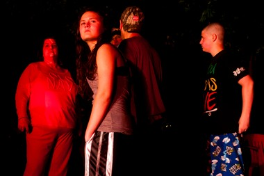Members of the Adams family look out from their driveway as they assess the damage to their neighborhood Tuesday evening on W. Thompson Road in Fenton Township.